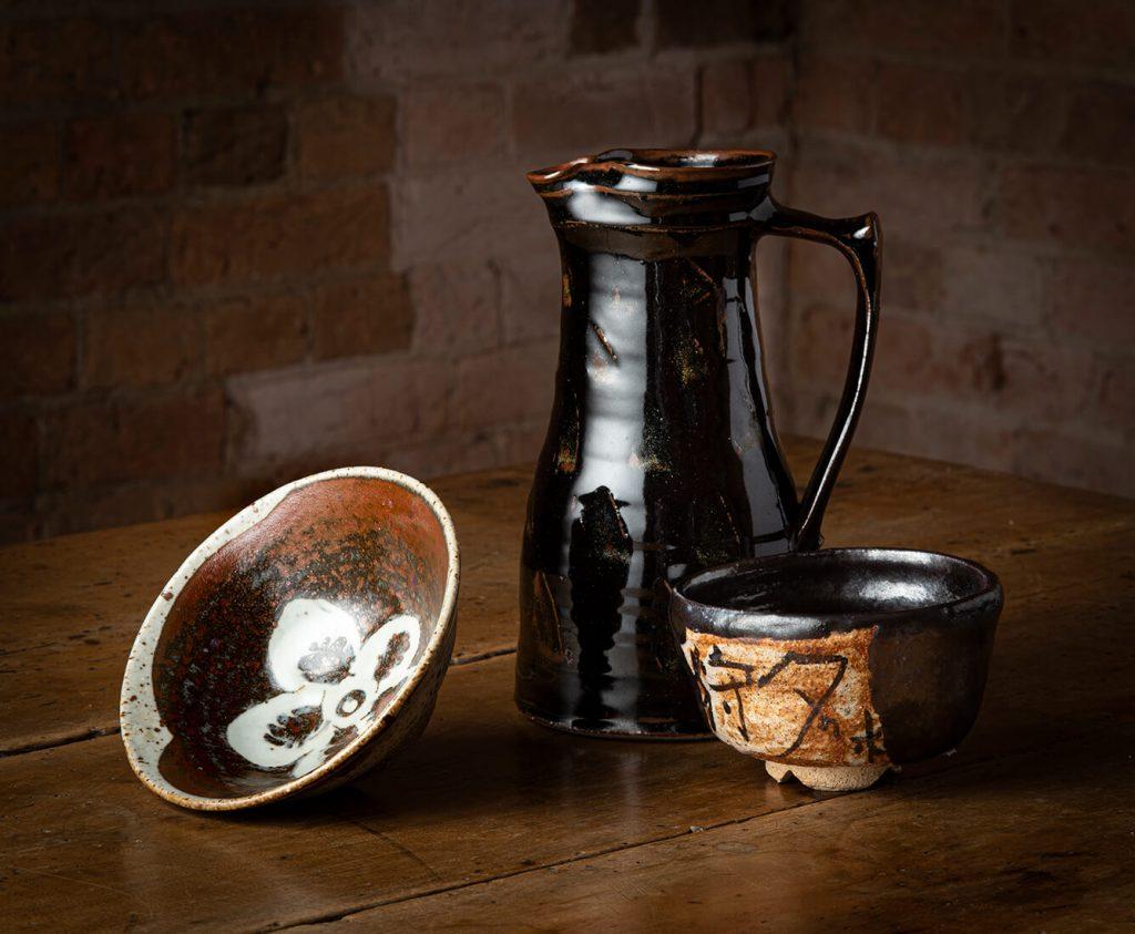 L-R: Takeichi Kawai, Bowl, local stoneware, iron and ash glazes, 1964; Ian McKay, Jug, stoneware, tenmoku glaze, 1964; Yasuo Terada, Teabowl, stoneware, black Oribe glaze, 2008. Image, Ashley Mackevicius