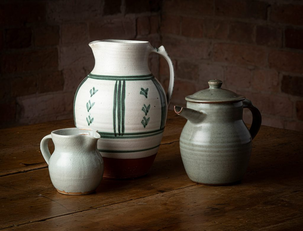L-R: Ivan McMeekin, Jug, local porcelaneous stoneware, 1956; Gwyn Hanssen Pigott, Jug, earthenware, tin glaze majolica, 1956; Ivan McMeekin, Teapot, local stoneware, c1954-59. Image, Ashley Mackevicius