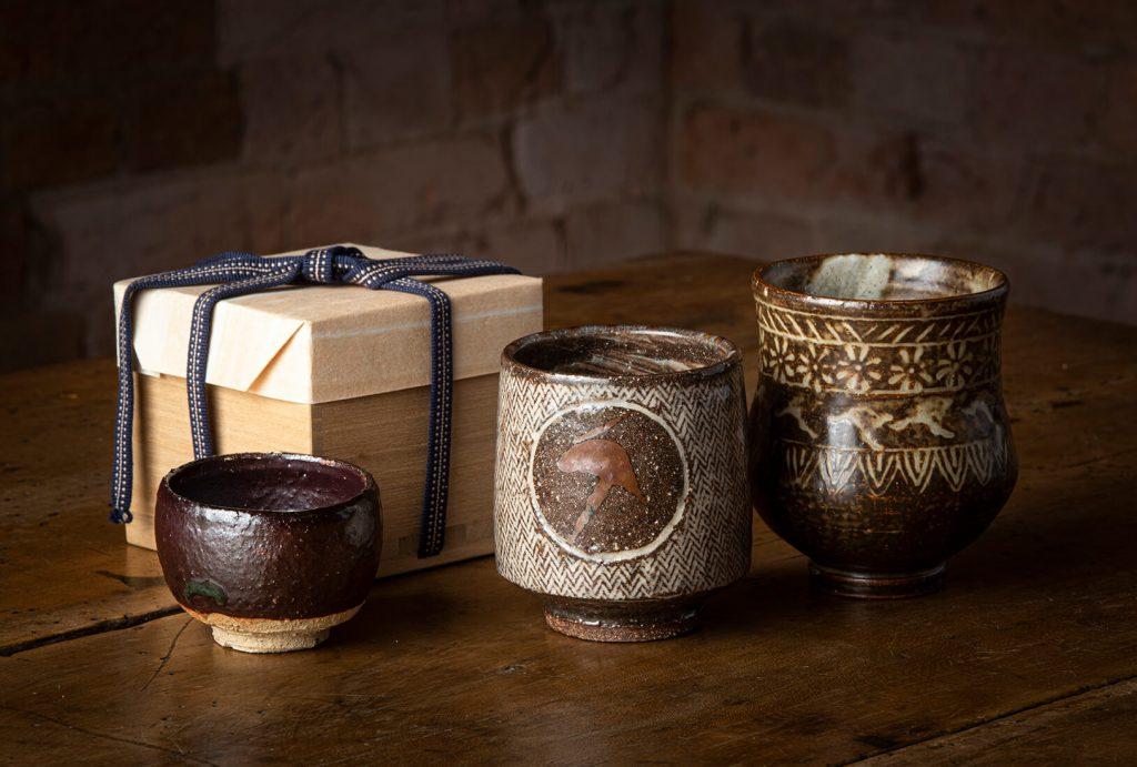 L-R: Yasuo Terada, Sake cup, stoneware, 2008; Tatsuzo Shimaoka, Teacup, dark stoneware, white slip, Mishima (rope inlay) design, 1970s; Shigeo Shiga, Beaker, stoneware, white slip, Australian penny design, 1966. Image, Ashley Mackevicius